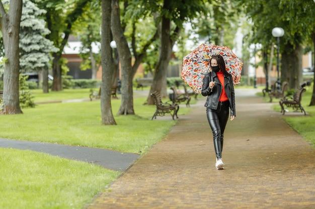 Wzdłuż ulicy idzie zamaskowana dziewczyna. dziewczyna w masce ochronnej chodzi w parku z parasolką w deszczu. zakażenie koronawirusem covid-19