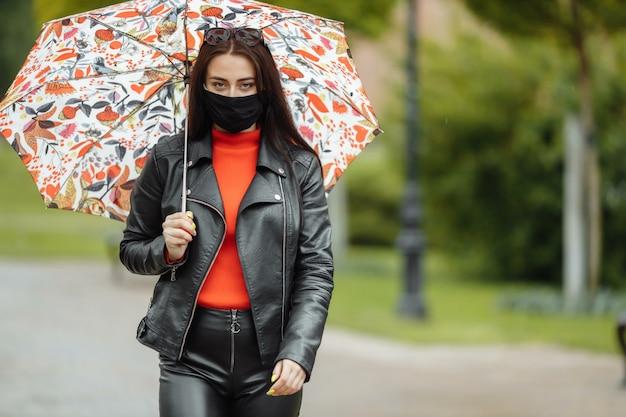 Wzdłuż ulicy idzie zamaskowana dziewczyna. dziewczyna w masce ochronnej spaceruje po parku z parasolem w deszczu. zakażenie koronawirusem covid-19.