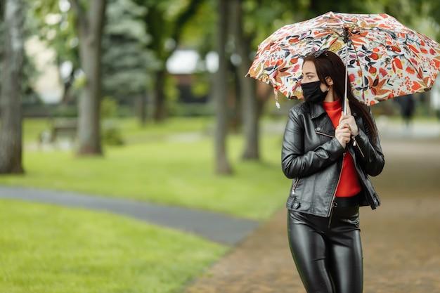 Wzdłuż ulicy idzie zamaskowana dziewczyna. dziewczyna w masce ochronnej spaceruje po parku z parasolem w deszczu. zakażenie koronawirusem covid-19
