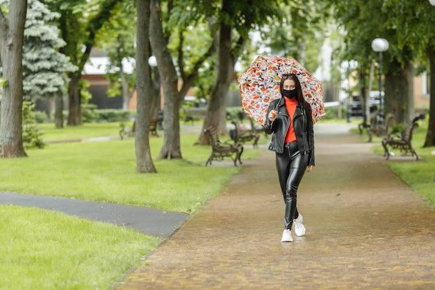 Wzdłuż ulicy idzie zamaskowana dziewczyna. dziewczyna w masce ochronnej spaceruje po parku z