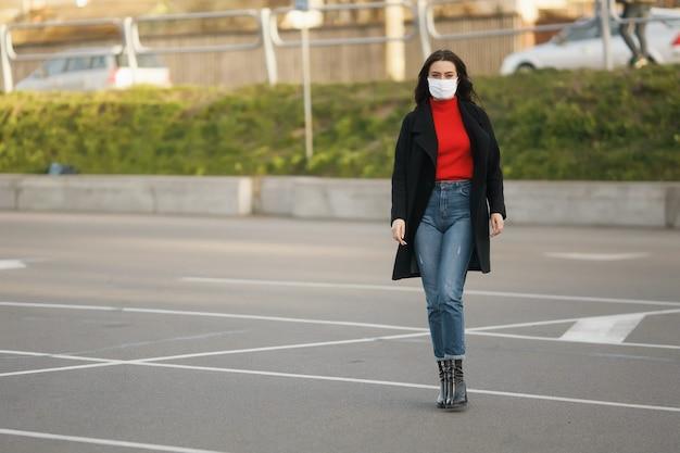 Wzdłuż ulicy idzie zamaskowana dziewczyna. zakażenie koronawirusem covid-19.