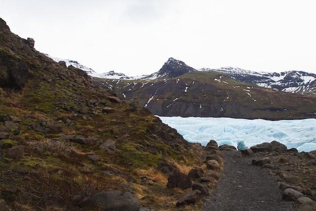 Wzgórza pokryte śniegiem i trawą otoczone zamarzniętym jeziorem w parku narodowym vatnajökull