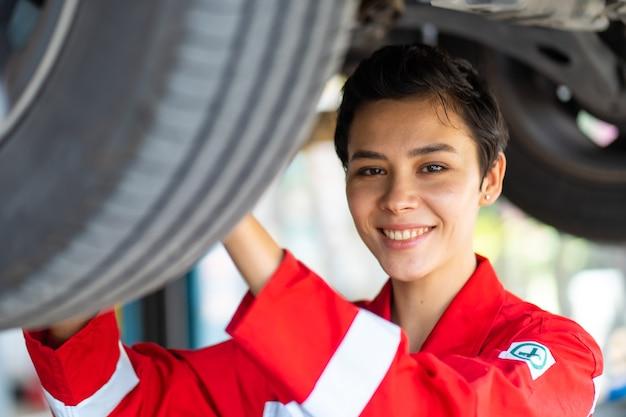 Wzmocnienie kaukaskiej kobiety mechanika w czerwonym mundurze, pracującego pod pojazdem na stacji obsługi samochodów