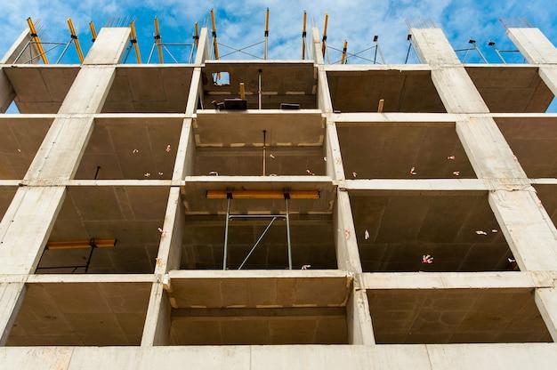 Wzmocniona rama nowego monolitycznego domu w budowie na tle błękitnego nieba