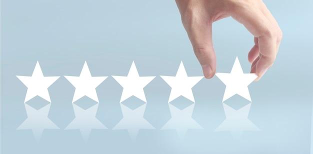 Wznieś się na zwiększenie pięciu gwiazdek w ludzkiej dłoni, zwiększ koncepcję klasyfikacji oceny oceny