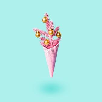Wznoszący się malowany różowy rożek do lodów z choinką i złotymi kulkami. minimalna koncepcja wakacje. nowoczesna karta z pozdrowieniami.