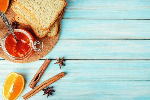 Wznoszący toast chleb i dżem z pomarańcze dla śniadaniowego błękitnego drewnianego tła