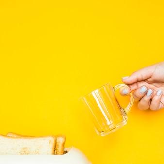 Wznoszący toast chleb wtyka z tostera na żółtym tle
