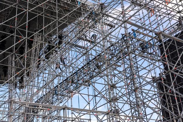 Wznoszenie sceny na koncert. instalatorzy na rusztowaniu
