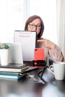 Wznów laptopa trzymając kobietę w średnim wieku 50 lat oraz aplikację pustą cv w miejscu pracy