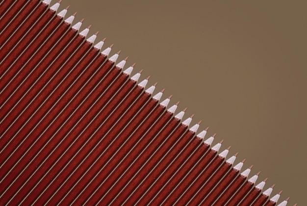 Wzór brązowych ołówków na szarym tle