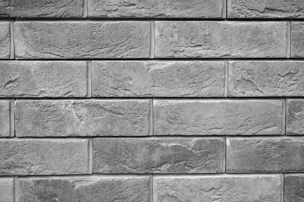 Wzór dekoracyjnej szarej łupkowej kamiennej ściany powierzchni jako tło. zabarwiony na szaro