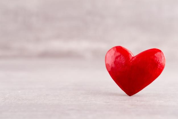 Wzór drewniane serca, jedno czerwone serce na tle drewniane serce