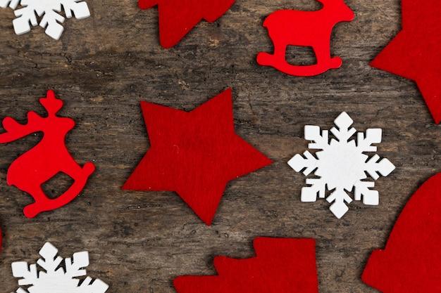 Wzór filcowe boże narodzenie dekoracje kłaść na drewnianym tle. świąteczny jeleń, płatek śniegu, gwiazda