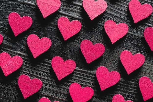 Wzór fioletowych serc na czarnym drewnianym stole