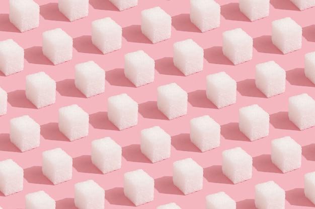 Wzór geometryczny wykonany z kostek cukru białego na pastelowym różowym tle. abstrakcyjne, minimalne.