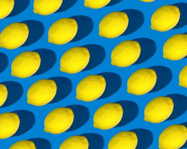 Wzór jasnożółtych cytryn z wyraźnym cieniem na jasnoniebieskim tle. zestaw cytryny, zdrowa żywność.