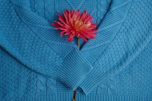 Wzór kolorowy trykotowy puloweru zbliżenie. ręcznie robiony produkt z wełny merynosowej. stos złożonych ubrań z kwiatami.