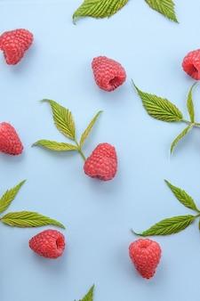 Wzór malin i zielonych liści na niebieskim tle. letnie jagody płaskie leżące - maliny czerwone. kreatywny minimalizm.