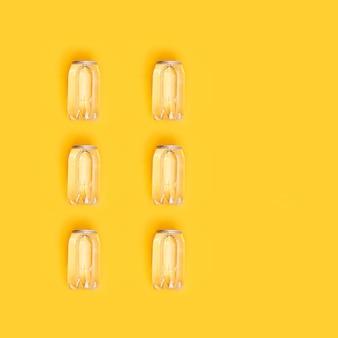 Wzór pocztówki z puszką wody na żółtym tle. letnie drinki. obraz monochromatyczny. kreatywny widok z góry.