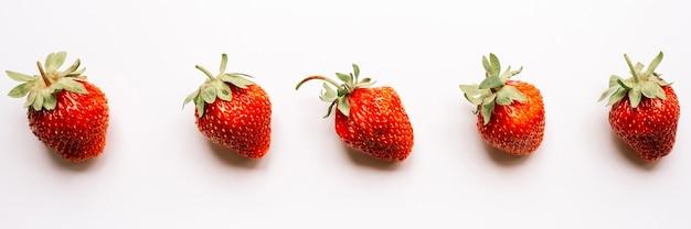 Wzór prawdziwy uczciwy gospodarstwo ekologiczne truskawki jagodowe na białym tle na białym tle. sezonowe letnie jedzenie widok z góry, leżał płasko. transparent