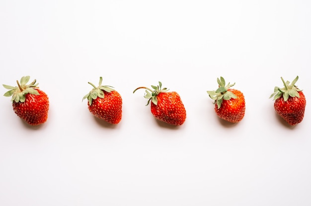 Wzór prawdziwy uczciwy gospodarstwo ekologiczne truskawki jagodowe na białym tle na białym tle. sezonowe letnie jedzenie widok z góry, płaskie lay