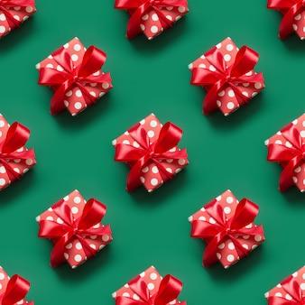 Wzór prezentów w czerwono-białym opakowaniu z kropkami i czerwoną kokardą na zielonej przestrzeni