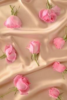 Wzór różowych róż spontanicznie ułożonych na satynowym beżowym tle. letnie wiosenne kwiaty elegancka koncepcja.