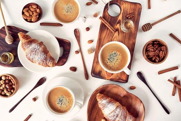 Wzór śniadaniowy, rogalik, kawa, miód, laski cynamonu, orzechy, cukier