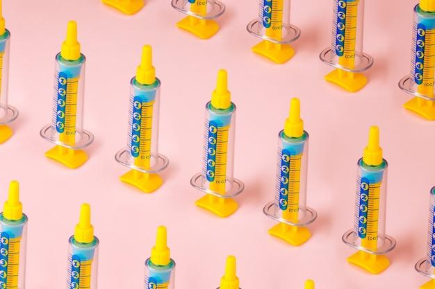 Wzór strzykawki na różowym tle, koncepcja szczepionki