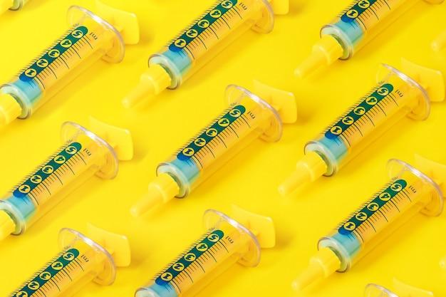 Wzór strzykawki na żółtym tle, medycyna koncepcja