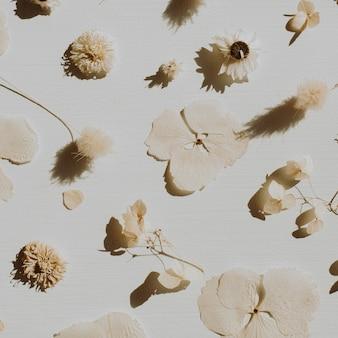 Wzór suchych płatków kwiatów na zakurzonej szarości.