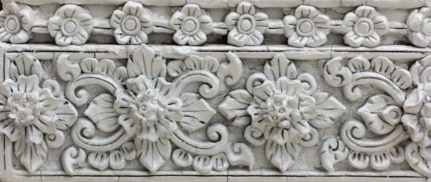 Wzór szarego kwiatu wyryty na stiukowej konstrukcji tubylczej ściany
