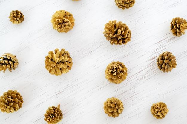 Wzór szyszek sosny złota na białym tle. płaskie lay desi