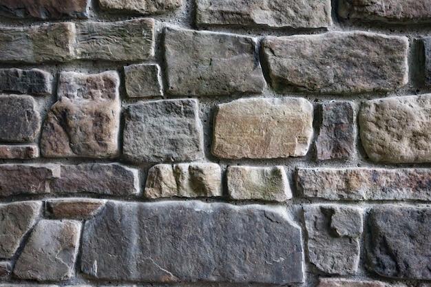 Wzór w kolorze szarym o nowoczesnym stylu, dekoracyjna nierówna popękana powierzchnia prawdziwej kamiennej ściany z cementem