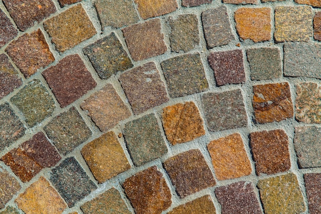 Wzór wielokolorowy starej kamiennej ściany nierównej pękniętej prawdziwej kamiennej ściany z cementem