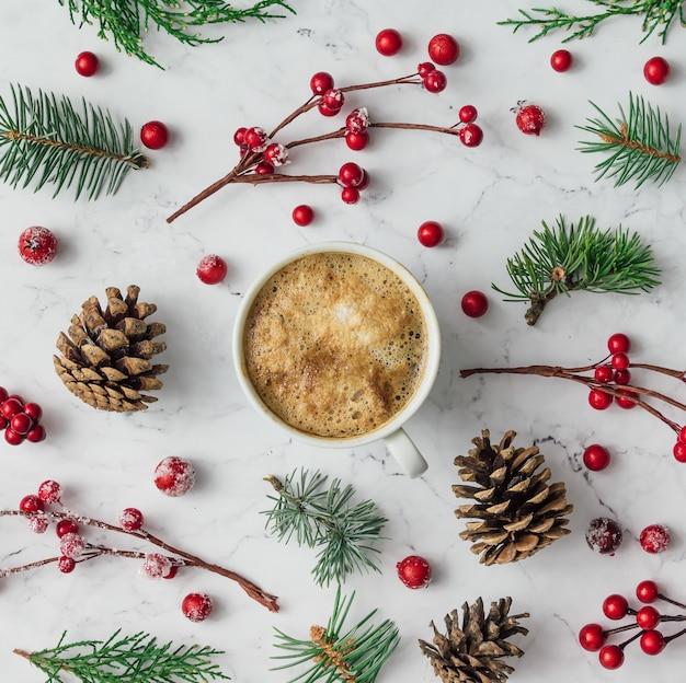 Wzór wykonany z gałęzi choinki, szyszek i czerwonych jagód z filiżanką kawy. koncepcja bożego narodzenia. leżał na płasko.