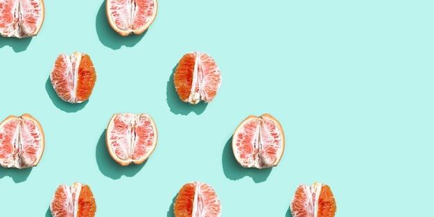 Wzór z czerwienią bez skórki pomarańczy lub grejpfruta na jasnym turkusowym kolorze.