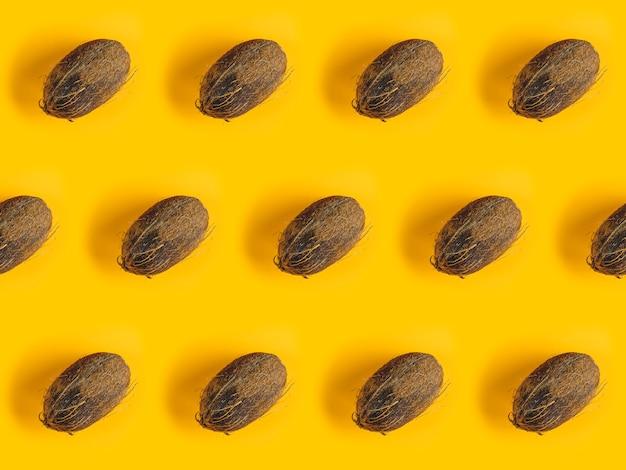 Wzór z dojrzałymi kokosami na żółtym tle. kokos w minimalistycznym stylu płasko leżącym