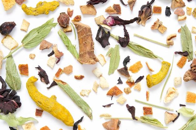 Wzór z herbatą ziołową, suchymi ziołami i kwiatami z kawałkami owoców i jagód. widok z góry.