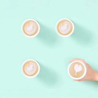 Wzór z kawą cappuccino na wynos w ekologicznym kubku termicznym wielokrotnego użytku