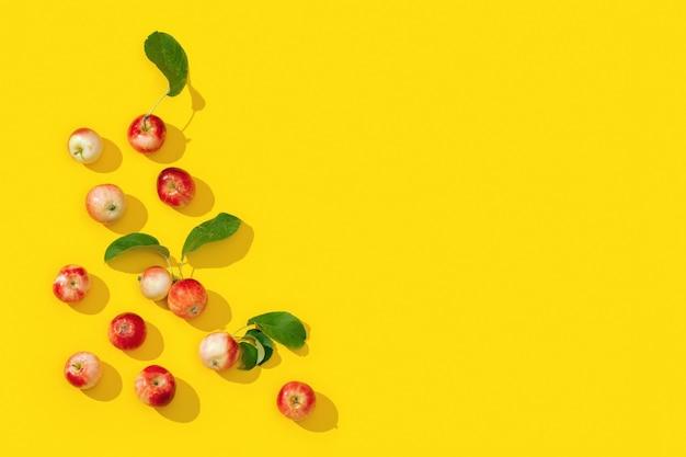 Wzór z małych czerwonych jabłek i zielonych liści z ciemnymi cieniami na żółto