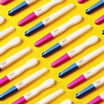 Wzór z pozytywnymi testami ciążowymi na żółtym tle