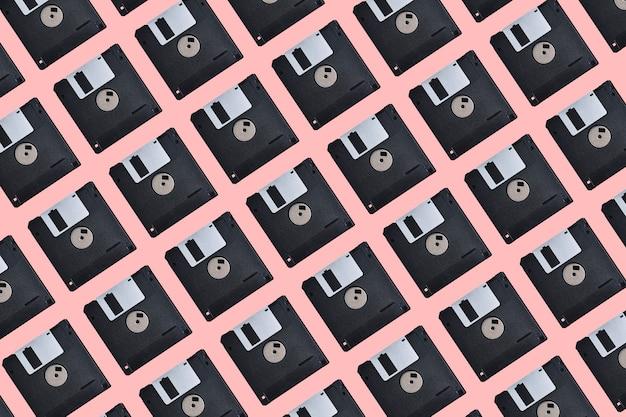 Wzór z wieloma dyskietkami na różowym tle. dyskietka komputerowa retro
