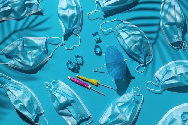 Wzór z wieloma maskami medycznymi, kostkami lodu i parasolami plażowymi na niebieskim tle