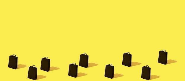 Wzór z wyprzedażą czarnych toreb na zakupy na żółto-pomarańczowym formacie banera w tle