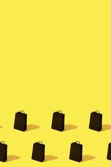 Wzór ze sprzedażą czarnych toreb na zakupy na żółtym tle z pionowym formatem przestrzeni kopii