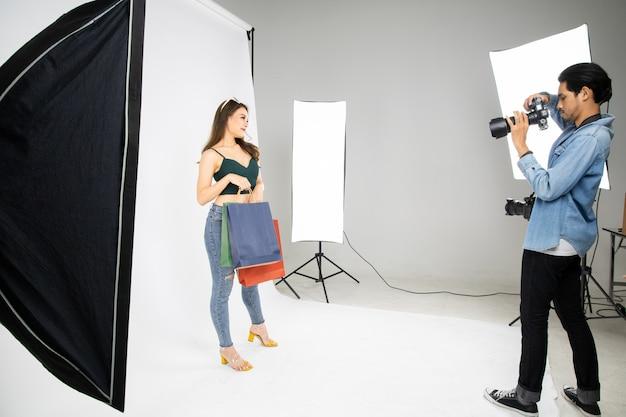 Wzorcowa młoda kobieta pozuje dla fotografii brać z fachowym fotografem w studiu.