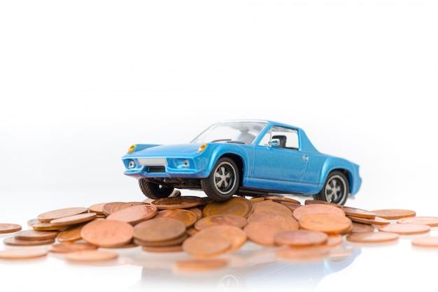 Wzorcowy błękitny parking samochodowy na sterty złotych monetach odizolowywać na białym tle.
