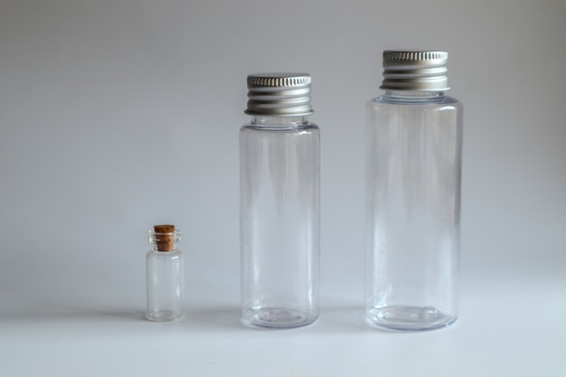 Wzorcowy wizerunek przejrzysta szklana butelka z metalową pokrywką na bielu